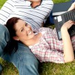 Couple of cheerful students using a laptop lying on the grass — Stock Photo
