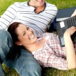 Stock Photo: Couple of happy students using a laptop lying on the grass