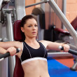 Beautiful athletic woman using a bench press - Stock Photo
