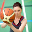 Stock Photo: Portrait of concentrated young womplaying basket-ball