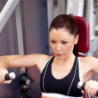 Serious athletic woman using a bench press - Stock Photo