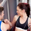 Cute athletic woman using a bench press with her coach — Stok fotoğraf