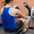 Athletic caucasian man using a rower - Stok fotoğraf