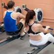 Sportsmen using a rower — Stockfoto