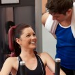 Joyful athletic woman using a shoulder press with her coach — Stock Photo