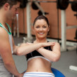 Joyful young woman sitting on a musculation ball with her coach — Stock Photo