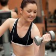 Portrait of a positive woman working out with dumbbells — Stock Photo