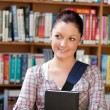 Joyful young caucasian woman holding a book - Stock Photo