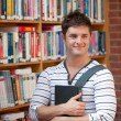 Attractive man holding a book - Stock Photo