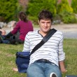Stock Photo: Good-looking male student lying on grass with his schoolbag