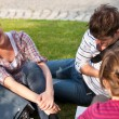 Stock Photo: Laughing couple of students sitting on grass talking with a fema