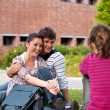Happy couple of students sitting on grass talking with a female — Stock Photo #10834560