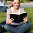 Young female student reading a book sitting on grass — Stock Photo