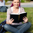 Stock Photo: Serious female student reading a book sitting on grass