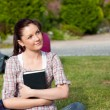 Thoughtful female student reading a book sitting on grass — Stock Photo #10834569
