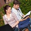 Young couple of students reading a book and using a laptop - Stok fotoğraf