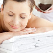 Smiling caucasian woman lying on a massage table in a spa center — Stock Photo #10834664