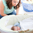 Young mother looking at her little son sleeping in his bed — Stock Photo