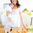 Caring young mother preparing vegetables for her baby in the kit — Stock Photo