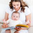 Loving mother reading a story to her adorable baby sitting on th — Stock Photo #10834681