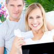 Stock Photo: Enamored couple lying on sofwith laptop and card