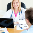 Smiling female doctor using her laptop and talking to her male p - Stock Photo