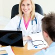 Smiling female doctor using her laptop and talking to her male p — Stock Photo