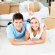 Jolly couple lying on the floor between boxes — Stock Photo #10834739