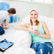 Smiling woman relaxing on a sofa while boyfriend painting the ro — Stock Photo #10834764