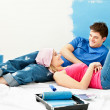 Stock Photo: Happy couple relaxing after painting a room