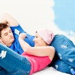 Young caucasian couple relaxing after painting a room — Stock Photo