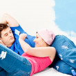 Young caucasian couple relaxing after painting a room — Stock Photo #10834807