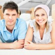 Smiling couple lying on the floor after unpacking boxes — Stock Photo #10834814