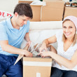 Stock Photo: Joyful caucasicouple unpacking boxes with glasses