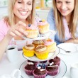Stock Photo: Positive young women eating cakes in the kitchen