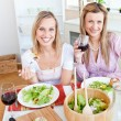 Pretty women eating a salad and drinking wine in the kitchen - Foto Stock