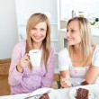 Happy female friends eating a chocolate cake and drinking in the — Stock Photo