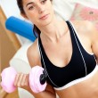 Serious athletic woman holding a dumbbell in her living-room — Stock Photo