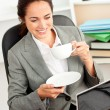 Smiling businesswoman holding a coffee while using a laptop at w — Stock Photo