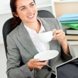 Businesswoman holding a cup of coffee in front of her laptop sit — Stock Photo