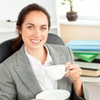 Happy businesswoman holding a cup of coffee sitting in her offic - Stock Photo