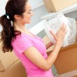 Joyful young woman unpacking boxes with glasses — Stock Photo