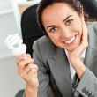Beautiful businesswoman holding a light bulb in her hand sitting — Stock Photo