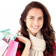 Joyful woman wearing a scarf and holding shopping bags smiling a — Stock Photo
