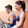 Stock Photo: Young athletes exercising on running machine with earphones