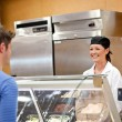 Portrait of a smiling food retailer with a male customer — Stock Photo #10835049