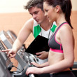 Beautiful female athlete standing on a running machine talking w — Stock Photo #10835051