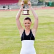 Cheerful female athlete holding a trophee — Stock Photo #10835103