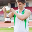 Sporty man holding a cup and a medal standing — Stock Photo