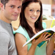 Stock Photo: Caucasicouple looking for book